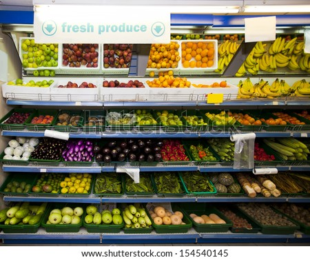 Various vegetables and fruits on display in grocery store - stock photo
