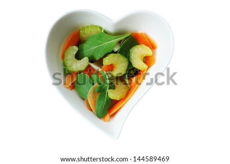 Various vegetables salad in heart shape bowl isolated on white background - stock photo