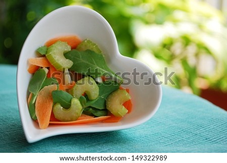 Various vegetables salad in heart shape bowl on green natural background - stock photo