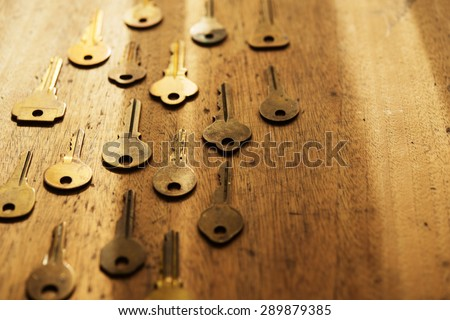Various vintage brass keys aligned in the same direction on a old wooden desk. Security and encryption, concept image. Shallow depth of field. - stock photo