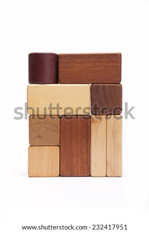 Various wood blocks(oak, walnut, teak, pine) like a building(wall) isolated white at the studio. - stock photo