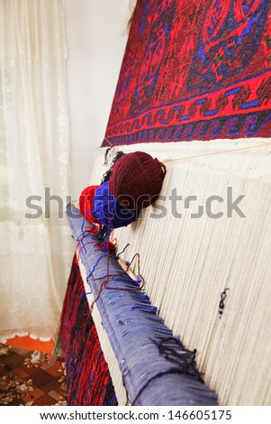 Various yarn on loom with carpet sideview - stock photo