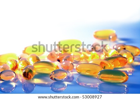 Various yellow and orange pills and capsules on a blue and white background with saturated colors and copy space - stock photo