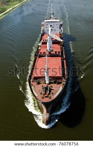VARNA, BULGARIA - APR 22: Cargo ship LINDEN (Year Built: 1977, Flag: Moldova) sails away into open sea after a short stay in Varna-west port on April 22, 2011 in Varna, Bulgaria. - stock photo