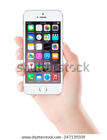 Varna, Bulgaria - December 07, 2013: Female hand holding Apple Silver iPhone 5S displaying iOS 8 mobile operating system, designed by Apple Inc. Isolated on white background. - stock photo