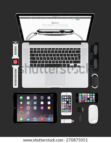 Varna, Bulgaria - February 09, 2015: Top view of Apple gadgets technology mockup consisting macbook pro with apple watch web page on the screen, ipad air 2, smart watch concept, iphone 5s, magic mouse - stock photo