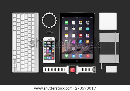 Varna, Bulgaria - February 09, 2015: Top view of Apple products mockup. Consists of ipad air 2, iphone 5s, keyboard, smartwatch concept, notebook, eraser, bracelet, reminder. - stock photo