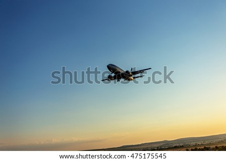 VARNA, BULGARIA - July 25, 2016: Quick civilian passenger plane in the sky landing to touch the ground. Airplane in the rays of the setting sun in landing mode in Varna airport
