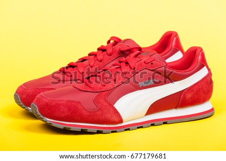 Varna , Bulgaria - JUNE 17, 2017. Red PUMA sport shoes on yellow background. Puma, a major German multinational company. Product shot