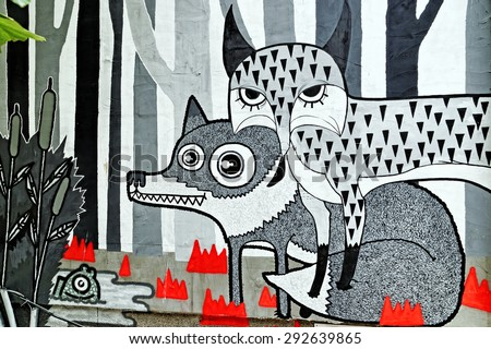 Varna, BULGARIA - June 21, 2015: Street art by unknown artist of fox and wolf in the woods close to a lake. - stock photo