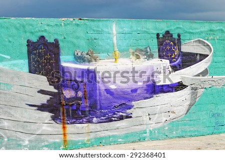 Varna, BULGARIA - June 21, 2015: Street art by unknown artist on a concrete wall close to Port of Varna. Dinner is served. The chairs and the table are stylish, but the meals are made from sea waste.  - stock photo
