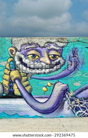 Varna, BULGARIA - June 21, 2015: Street art by unknown artist on a concrete wall close to Port of Varna of a captain holding a fishing net. - stock photo