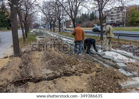 VARNA, BULGARIA - 23 November 2015: workers repairing sidewalk in city park. Replacing old paving slabs, construction of bicycle paths. Work communal urban services improvement