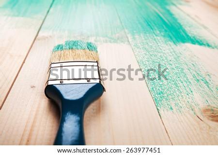 Varnishing a wooden shelf using paintbrush, turquoise color - stock photo
