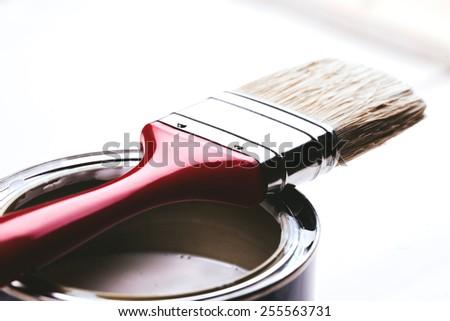 Varnishing and painting a wooden shelf using paintbrush - stock photo