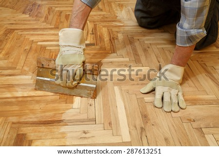 Varnishing of oak parquet floor, senior workers hand and tool