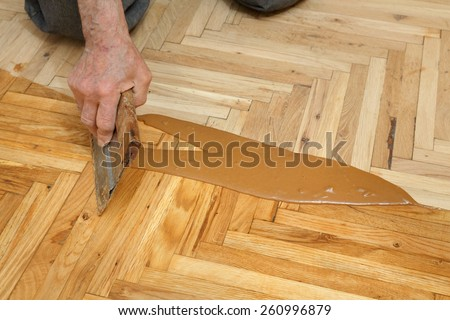 Varnishing of oak parquet floor, senior workers hand and tool, 77 year old senior worker - stock photo