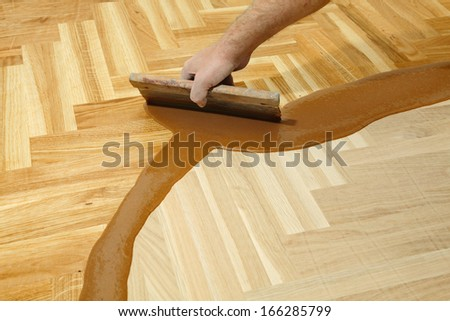 Varnishing of oak parquet floor, workers hand and tool - stock photo