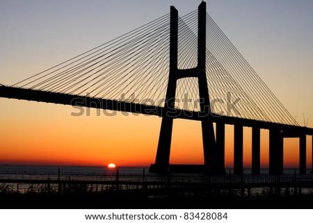 Vasco da Gama bridge, backlit by a mid June sunrise, at Lisbon, Portugal. Image unsharpened. - stock photo