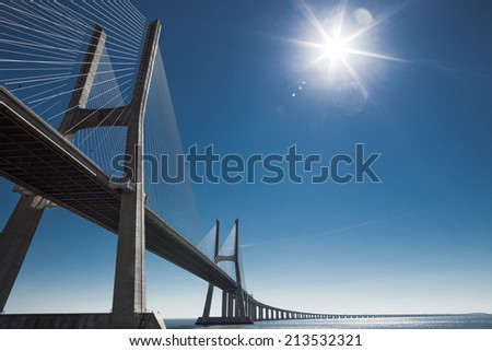 Vasco Da Gama bridge in backlight of the morning sky - stock photo