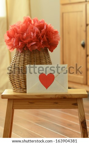 Vase basket with red tissue paper flower-pom pom and love letter with red heart sticker on small wooden step stool - stock photo