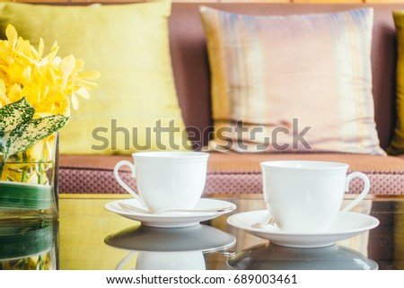 Vase flower and white coffee cup on table and pillow on sofa decoration of living room interior