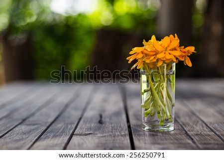 Vase full of colorful flowers on wood table - stock photo