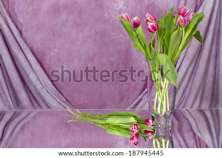 Vase of blue and white flowers against black background with yellow large mum type flower laying on mirror with its reflection - stock photo