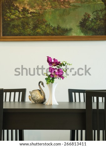 Vase of flower and silver carve statue swan on a table.Decorative interior dining room - stock photo