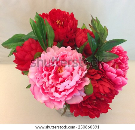 Vase of Pink and Red Artificial Flowers on White Cream Background