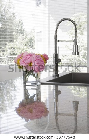 vase of pink peonies and chartreuse chrysanthemums on sink of modern kitchen - reflection in granite countertop - stock photo