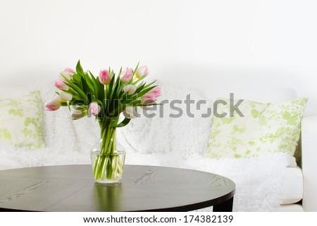 vase of tulips in modern white living room - home decor - stock photo