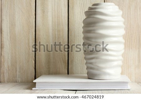 vase on book on wooden background.Monochrome