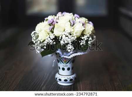 vase with a bouquet of fine flowers for wedding ceremony on a wooden table - stock photo