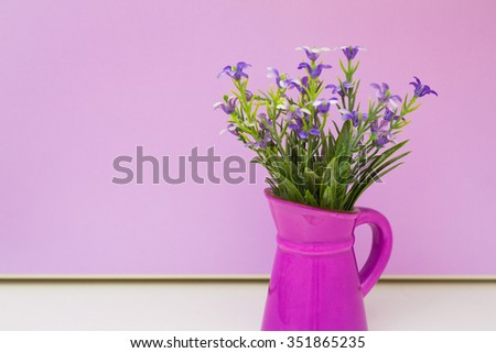 Vase with artificial flower violet background