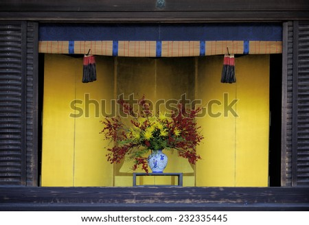 Vase with flowers against yellow background in the Imperial Palace, Kyoto, Japan - stock photo