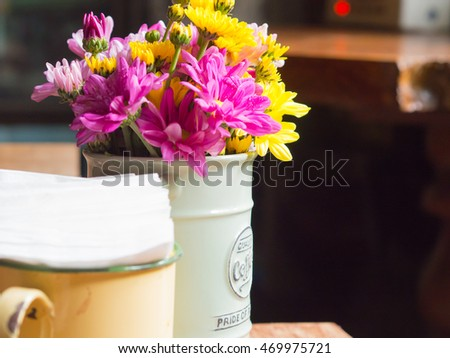 Vase with iron and flowers, vintage style on the table in coffee shops.