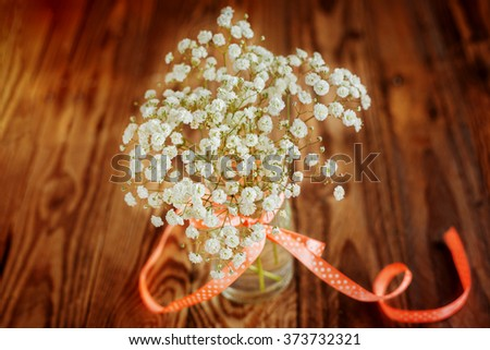 Vase with ribbon and with bunch of Gypsophila (Baby's-breath flowers) on wooden table - stock photo