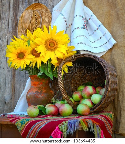 Vase with sunflowers and by a basket with apples - stock photo