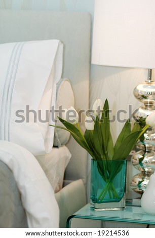 Vase with white tulips on the drawers in the bedroom - stock photo