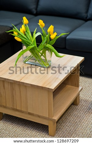 Vase with yellow spring tulips on modern wooden coffee table - stock photo
