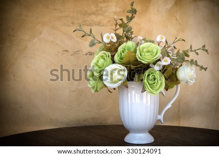 Vases artificial flowers on the wood desk with The wall is concrete. - stock photo