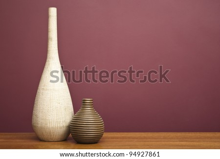Vases on a table in front of a burgundy wall - stock photo
