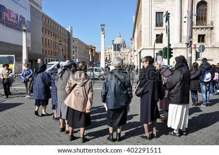 VATICAN CITY - MARCH 13, 2016: Tourists visiting the Saint Peter square and the Basilica San Pietro in Vatican city. Rome, Italy