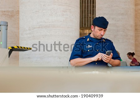 VATICAN CITY - SEPTEMBER 21: unidentified policeman using his mobile phone at St. Peter's Basilica security check in Vatican City, Italy on September 21, 2013. - stock photo