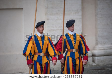 VATICAN CITY, VATICAN - SEPTEMBER 3: Famous Swiss Guard surveil basilica entrance on September 3, 2014 in Vatican. The Papal Guard with 110 men is the world's smallest army
