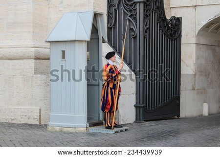 VATICAN CITY, VATICAN - SEPTEMBER 26: Papal Swiss guards stand guard at the entrance of Saint Peter's Basilica on September 26, 2012. Swiss Guards in their traditional uniform. - stock photo
