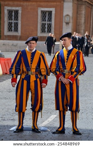 VATICAN - FEBRUARY 23: Pontifical Swiss Guards on February 23, 2014 in Vatican City. A small force maintained by the Holy See, it is responsible for the safety of the Pope. - stock photo