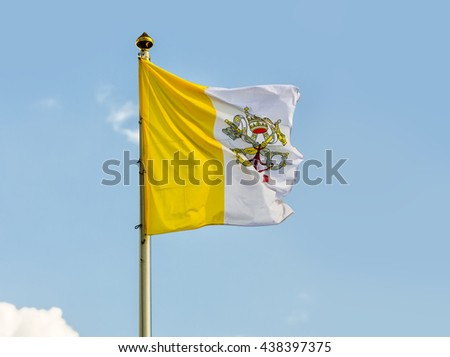 Vatican flag against blue sky. Flag of Vatican City was adopted on June 7, 1929, the year Pope Pius XI signed the Lateran Treaty with Italy, creating a new independent state governed by the Holy See