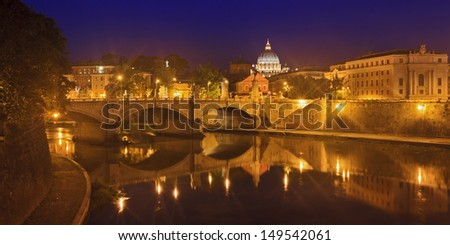 Vatican Italy Rome view at St Peter Basilica dome over tiber river bridge with street lamps illuminated and reflected in the water
